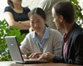 a man and woman looking at a laptop screen at an outside table area, this photo links to the PHD program web page