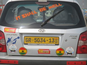 "A car with ""it shall be well"" posted on its rear window."