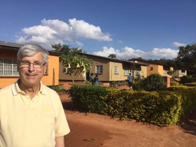Colin Glassco, MBA '67 stands in front of four of the residences his foundation built at the orphanage they support. Three students can be seen returning from school.