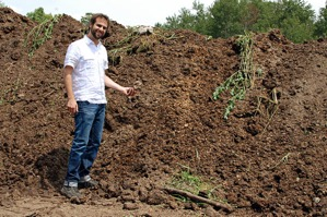 Daniel Bida stands in front of the manure that will be used to create renewable, sustainable energy.