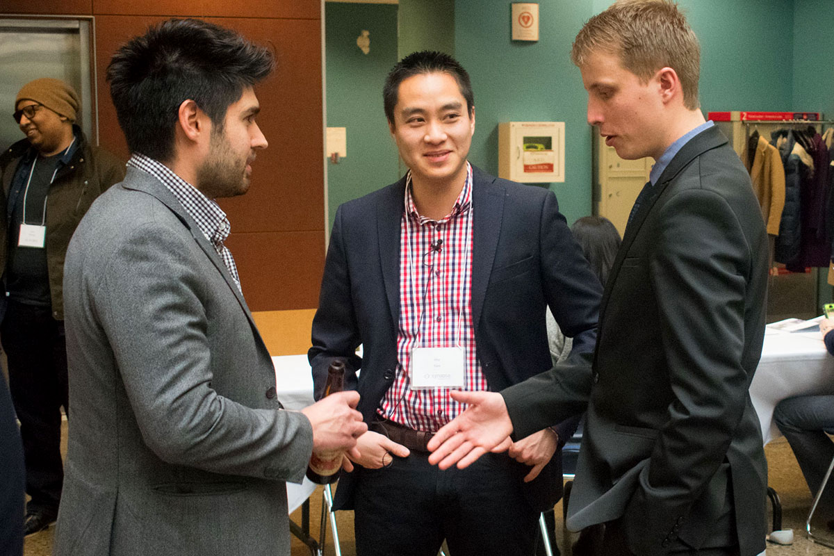 DeGroote MBA candidate Philipp Kolb, alongside Dr. Kha Tran, speaks with attendees after delivering the team's business pitch.