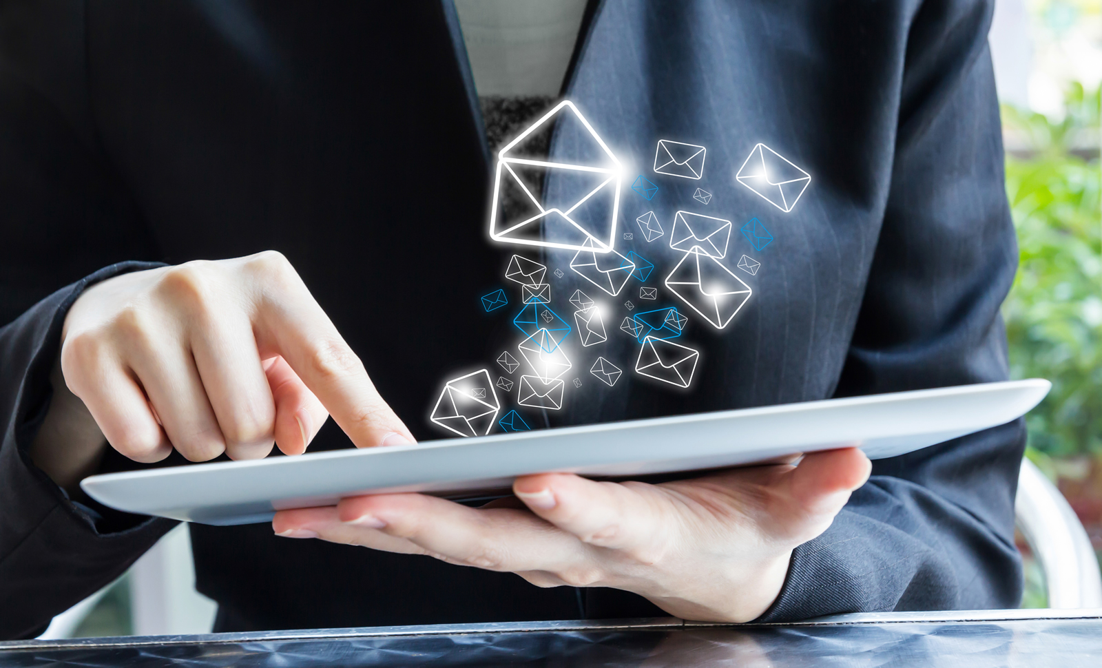 Woman working on an iPad (with shiny mail icons floating out of it).