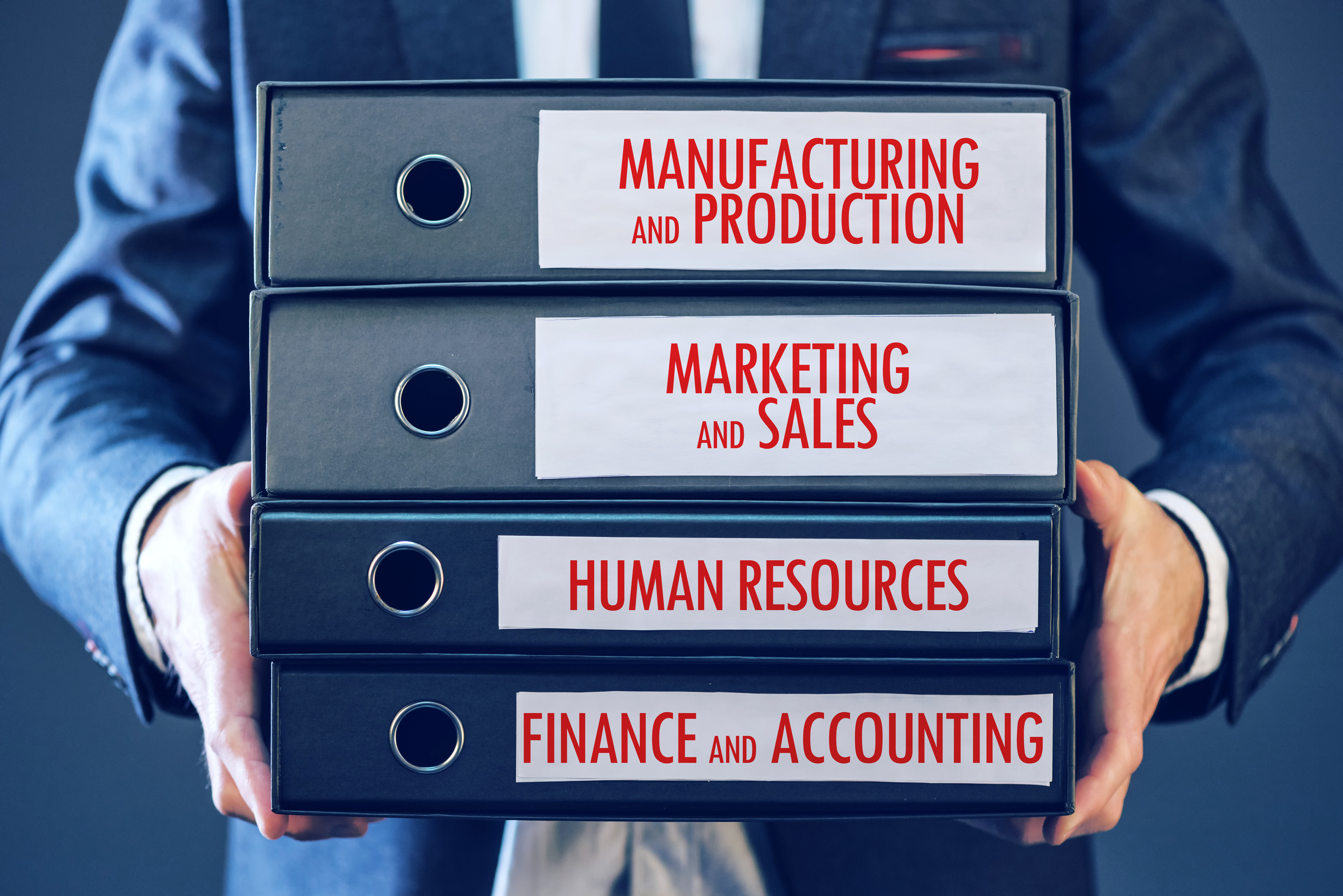 Businessman holding document binders with four major business functions - manufacturing production, marketing sales, human resources, finance accounting