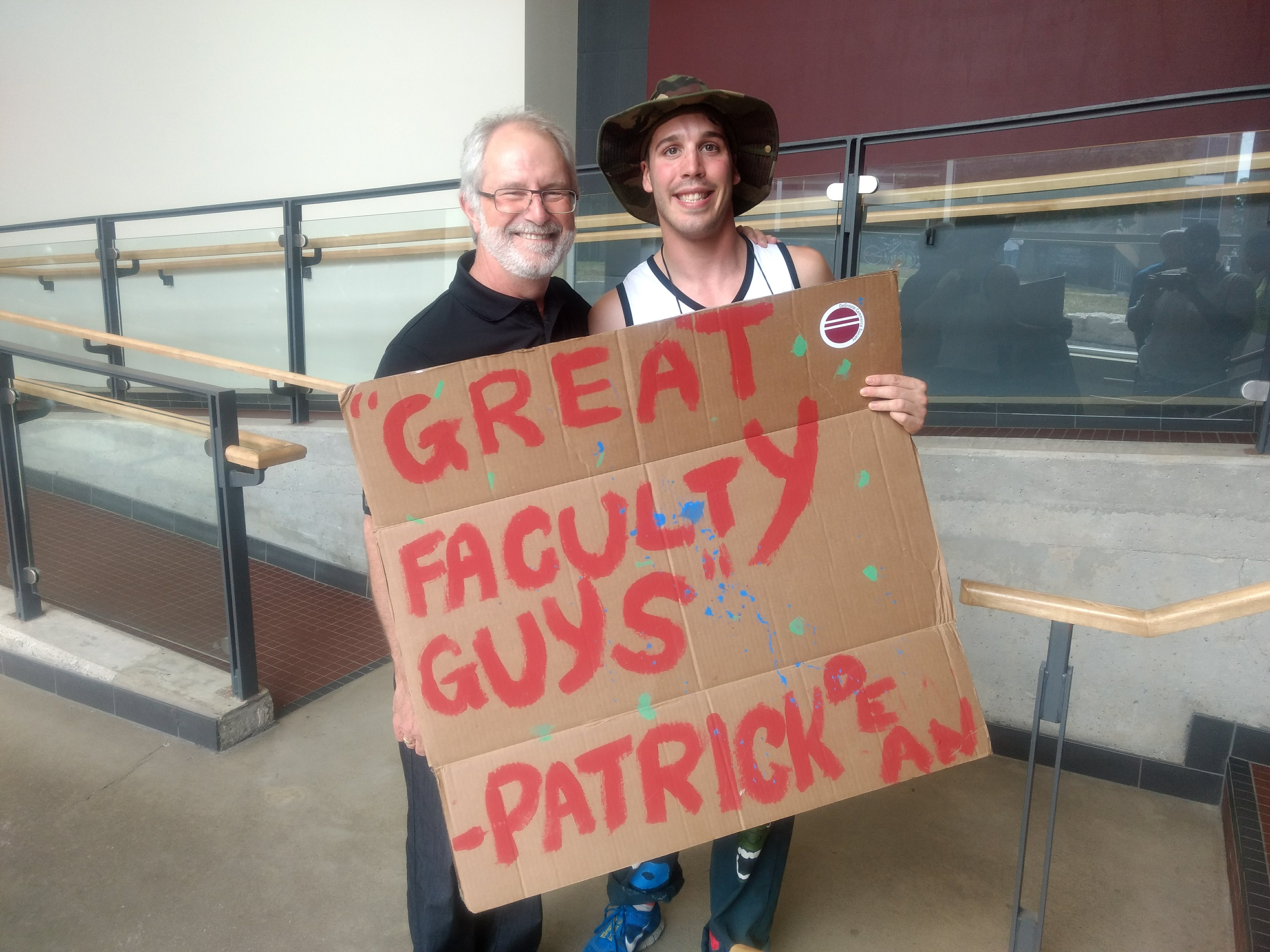 "Kevin pictured with McMaster President and Vice-Chancellor Dr. Patrick Deane holding a sign that says "" ""Great faculty guys,"" Patrick Deane"