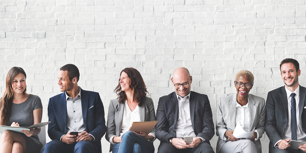 People in Business Clothes Sitting Along a Wall