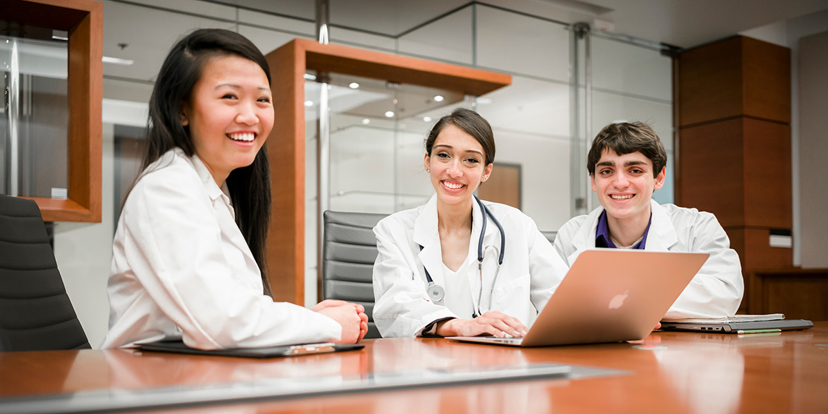 Three Students in White Coats Smiling at a Table