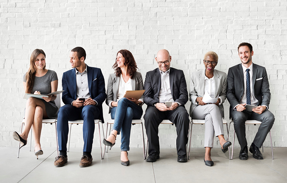 Diverse group of business people sitting on chairs and laughing