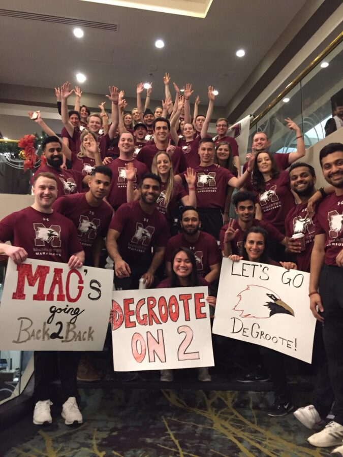 DeGroote students holding signs showing McMaster pride