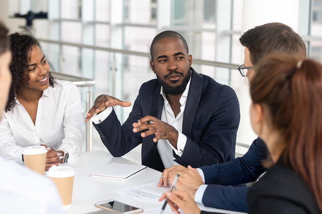Millennial boss leading corporate team during briefing in boardroom