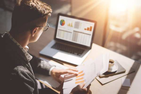 Young finance market analyst in eyeglasses working at sunny office on laptop while sitting at wooden table.Businessman analyze document in his hands.Graphs and diagramm on notebook screen