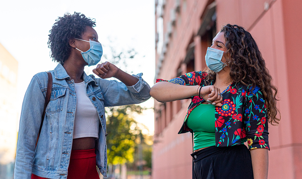 Two young women greeting each other by bumping elbows