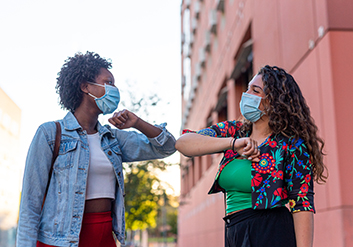 Two women doing an elbow shake with masks on