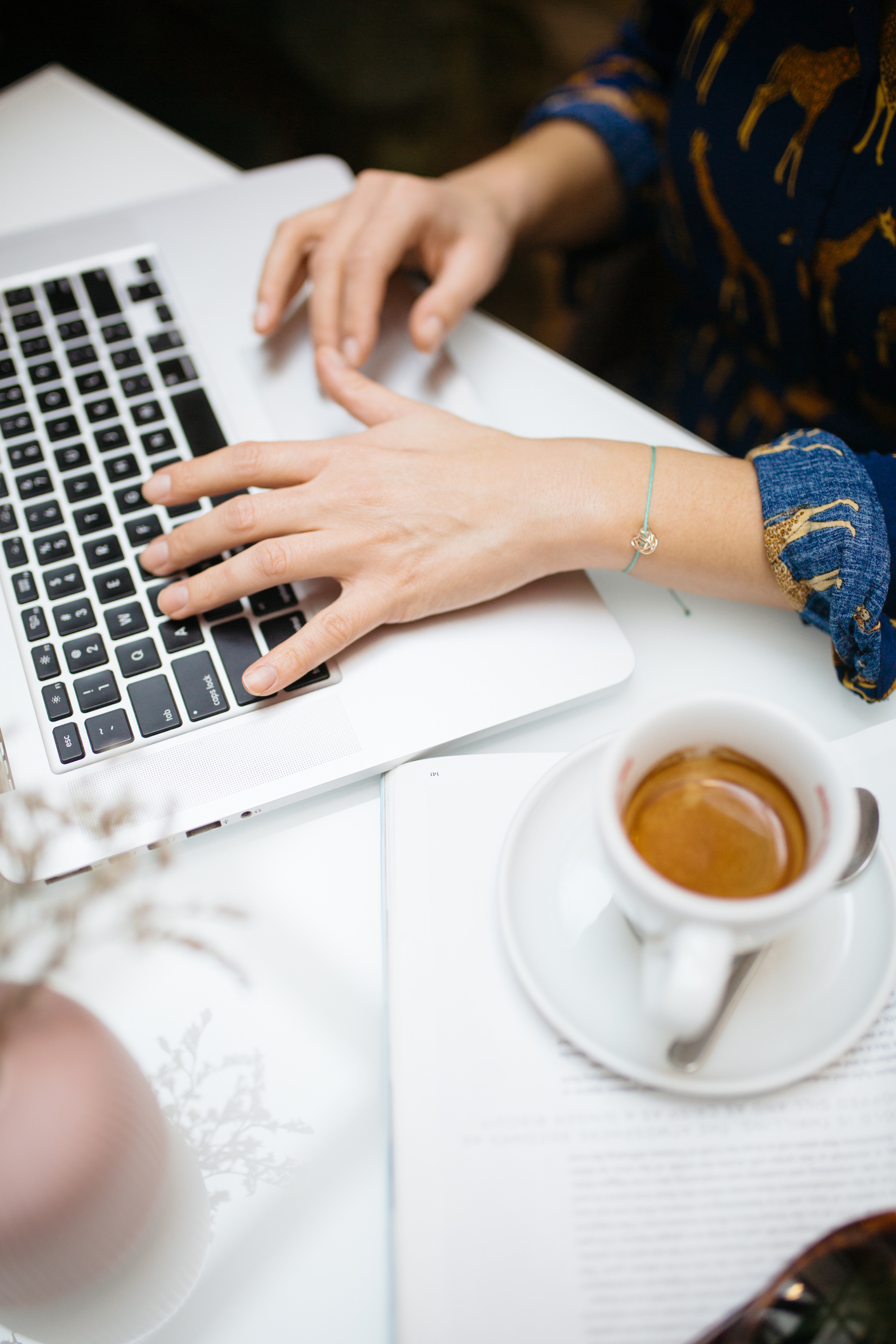 Woman working on laptop beside cup of coffee, hand on keyboard close up