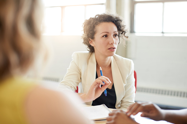 Female manager talking in a meeting with a pencil in her hand