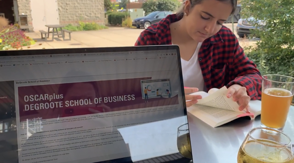A laptop screen open to the OSCARplus page for the DeGroote School of Business, with a women reading a book in the background