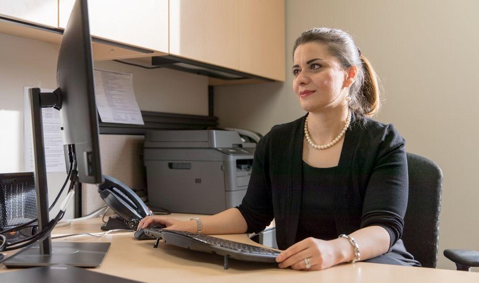 Professor Maryam Ghasemaghaei sitting at a desk analyzing data