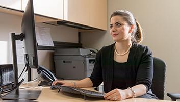 Professor Maryam Ghasmeaghaei sitting at a desk analyzing data